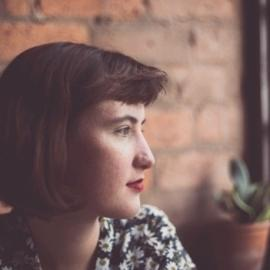 Woman's face side on against a brick wall with a cactus in the background.
