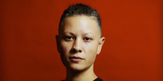 Person of colour with short black hair and a dark top, against a dark red background