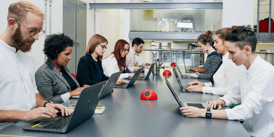 Group of people sitting at a table working on laptops