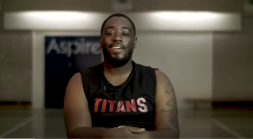 Black person on a basketball court speaking to the camera