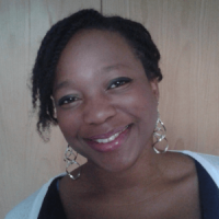 Black woman with short hair, gold earrings and a light-blue top smiles at the camera