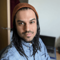 Person of colour with dreadlocks, in a blue shirt with a red beanie hat, looks at the camera from an inside room