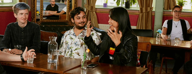 Two groups of people sitting together in a pub