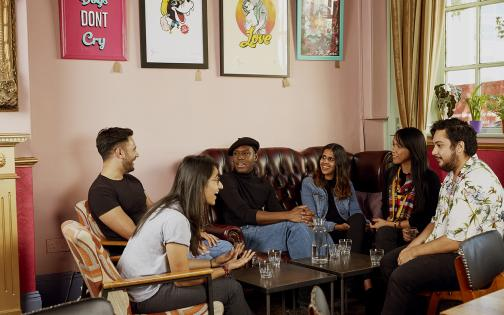 A group of people sat around a table in a coffee shop