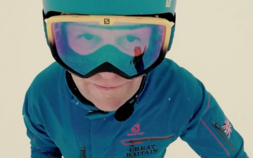 Person in skiing uniform wearing goggles on snow and looking up at the camera