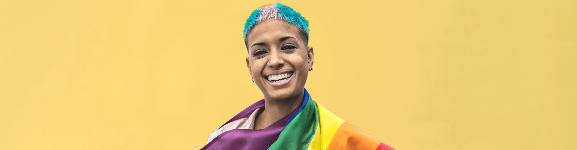 Person of colour with hair dyed in trans flag colours, draped in the rainbow flag, smiles at the camera