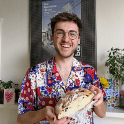 Person wearing a loud shirt and holding a loaf of bread, and smiling
